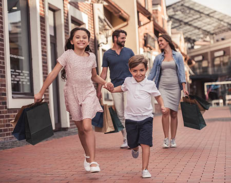 A happy family going on a shopping spree, teaching kids harmful financial habits