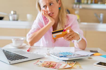 A woman looks overwhelmed while reviewing her credit card finances