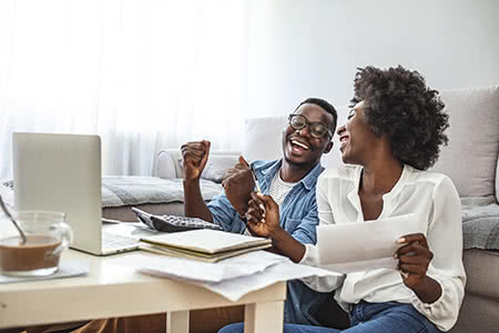 A couple celebrates while reviewing their savings information online